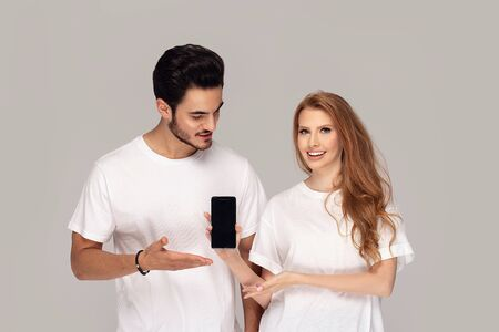 Happy young couple wearing white t shirts ,posing in studio, showing empty screen of mobile phone.