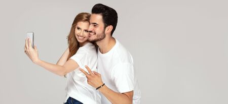 Happy young couple looking at camera of mobile phone, making selfie portrait, wearing white t shirts and jeans, posing in studio, having fun together. Facial expression. Love and friendship concept.