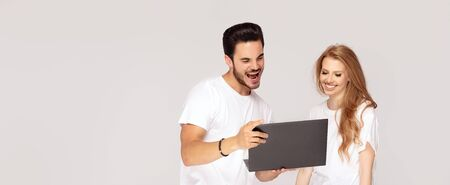 Happy young couple, caucasian guy and girl , looking at laptop screen. Studio shot. Copy space.