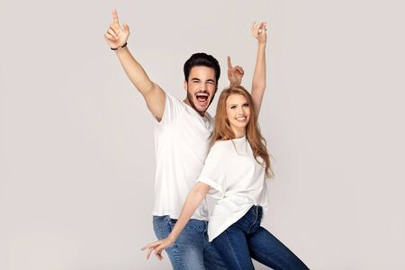Beautiful young happy couple isolated on studio background. Facial expression, human emotions, advertising concept. Man and woman with amazing toothy smiles. Stock Photo
