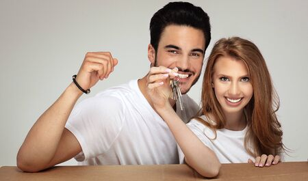 Happy smiling couple with keys to the new home. Studio shot.