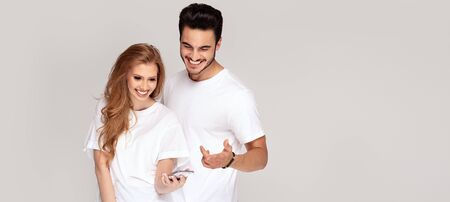 Happy young couple looking at mobile phone, wearing white t shirts and jeans, posing in studio, having fun together. Facial expression. Love and friendship concept. Stock Photo