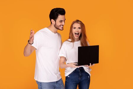 Happy beautiful couple wearing jeans and white shirts, posing in studio on yellow background, using laptop.