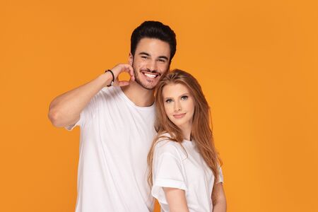 Happy beautiful couple wearing white shirts, posing in studio on yellow background.