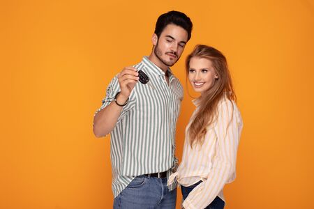 Happy young couple with car key on color background. Boyfriend showing the gift to smiling girlfriend.