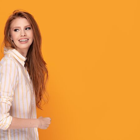 Happy smiling red hair girl. Beautiful female half-length portrait isolated on orange studio background.  Facial expression, human emotions concept.