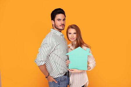 Young beautiful couple dreaming about first shared house. Photo in studio, colorful orange background. Home concept.