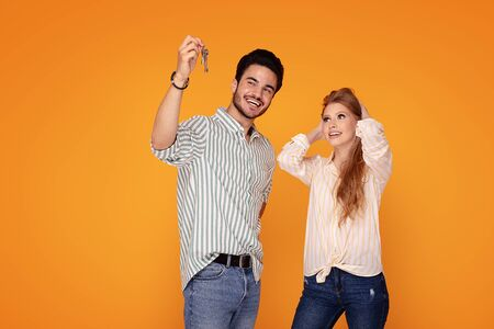 Happy young couple with house key on color background. Boyfriend showing the gift to smiling girlfriend.