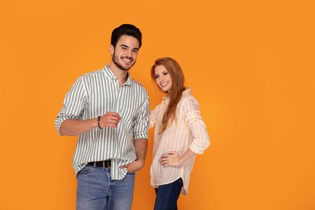 Beautiful young couple posing together on yellow studio background. Facial expression, human emotions concept. Happy people smiling, having fun.