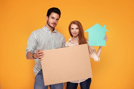 Young beautiful couple buying first shared house. Photo in studio, colorful orange background. Home concept.