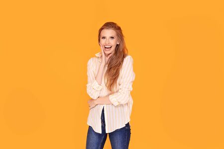 Smiling beautiful red hair woman posing on yellow background in studio. Human emotions, facial expression concept.