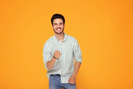 Happy handsome man smiling, posing on color studio background. Young satisfy man. Human emotions, facial expression concept.