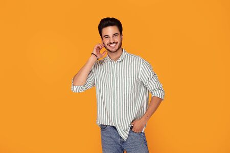Happy handsome man standing, smiling, posing on color studio background. Young satisfy man. Human emotions, facial expression concept. Stock Photo