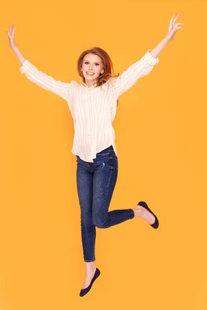 Smiling beautiful red hair woman jumping on yellow background in studio. Human emotions, facial expression concept.