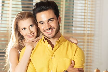 Young couple posing together in new home ,happy for moving to their first house.