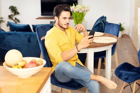 Portrait of cheerful young man relaxing at home, using mobile phone.