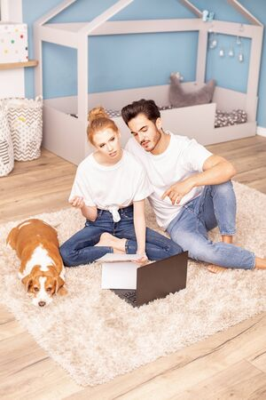 Young couple with cute beagle dog planning to arrange a childrens room. Family concept. Imagens