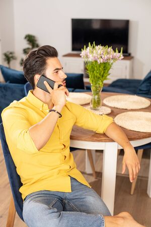 Portrait of cheerful young man relaxing at home,talking with someone by mobile phone.