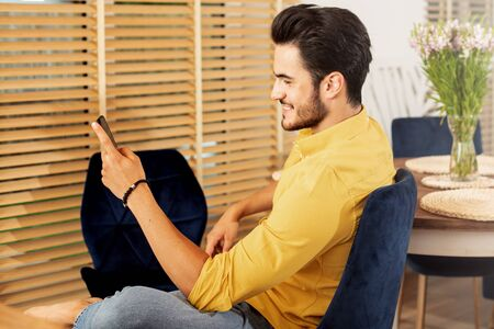 Portrait of cheerful young man relaxing at home, smiling and using mobile phone.