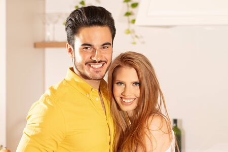 Young couple posing together, smiling and looking at camera. Imagens