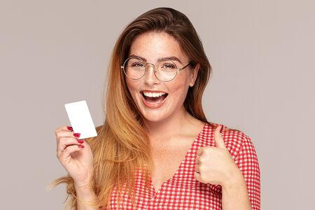 Beautiful young redhead woman in casual clothes holding credit bank card in hand, smiling to the camera, posing in studio. People lifestyle concept.
