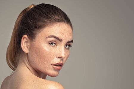 Beauty portrait of young attractive ginger woman with freckles on her face and body. Natural girl. Studio shot. Stock Photo