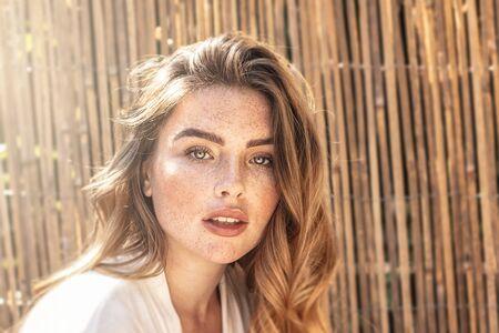 Retrato de joven atractiva con pelo rojo largo ondulado y pecas en el rostro. Mujer posando en un día soleado de verano.