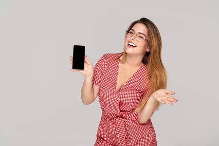 Smiling young woman with freckles holding mobile phone with blank empty screen isolated on studio background. People lifestyle concept.