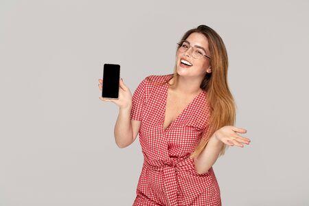 Sorridente giovane donna con lentiggini tenendo il telefono cellulare con schermo vuoto vuoto isolato su sfondo per studio. Concetto di stile di vita della gente.