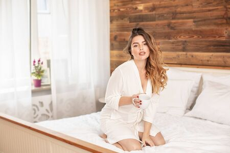 Pretty, calm, redhead woman relaxing at home on the morning. Girl with freckles holding white cup of coffee in hand, looking at camera, sitting in a cream robe in bedroom. Daily lifestyle, leisure time concept.