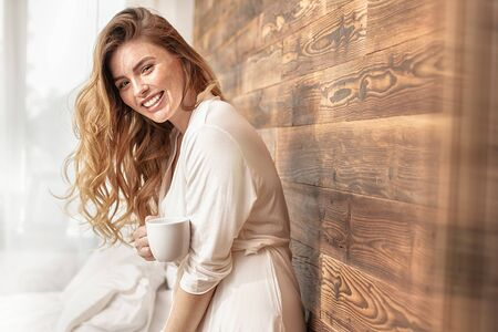 Pretty, calm, redhead woman relaxing at home on the morning. Girl with freckles holding white cup of coffee in hands, looking at camera, standing in a cream robe, posing in bedroom. Daily lifestyle, leisure time concept. Stok Fotoğraf
