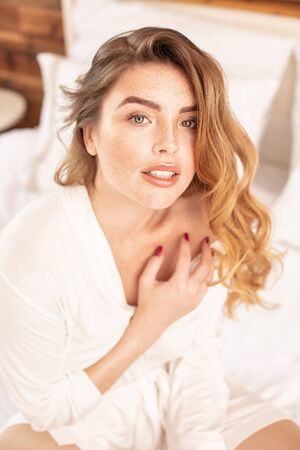 Attractive smiling redhead woman sitting on the bed at the cozy bedroom. Beautiful girl relaxing, morning leisure time. Beauty oortrait, wavy hairstyle. Stok Fotoğraf