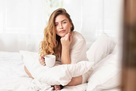 Attractive smiling redhead woman sitting on the bed at the cozy bedroom, drinking hot coffee. Beautiful girl relaxing, morning leisure time.