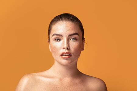 Closeup beauty portrait of girl with freckles on her face and body. Natural makeup. Ginger woman posing on orange studio background.