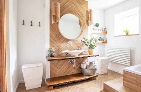 Biała umywalka na drewnianym blacie z zawieszonym nad nim okrągłym lustrem. Wnętrze łazienki.