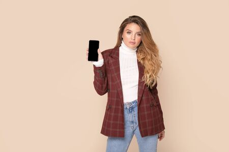 Young woman with freckles and long wavy hair holding mobile phone with blank empty screen isolated on studio background. Female student wearing fashionable clothes. People lifestyle concept. Stockfoto