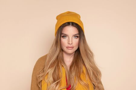 Fashion portrait of beautiful young woman with freckles on face, long hair and delicate makeup. Girl wearing yellow cap, scarf. Beige studio background. Autumn, winter style. Imagens