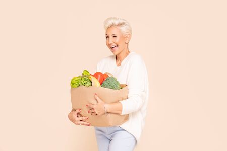 Smiling adult woman holding shopping bag full of groceries posing on beige background. Healthy food shopping. Paper package with vegetables and fruits, happy female buyer came from market.