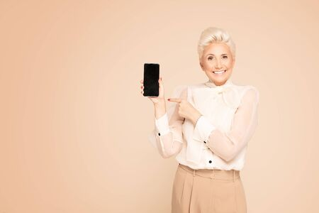 Portrait of elegant smiling adult woman with short blond hair holding cellphone , showing empty screen. Beige studio background. Banque d'images - 132165879