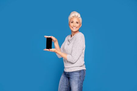 Casual mid age smiling woman with short blond hair holding cellphone , showing empty screen. Blue studio background. Banque d'images - 132165881