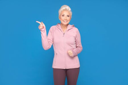 Studio shot of adorable energetic adult woman wearing sportswear, smiling to the camera. Blue background. Copy space. Banque d'images - 132165886
