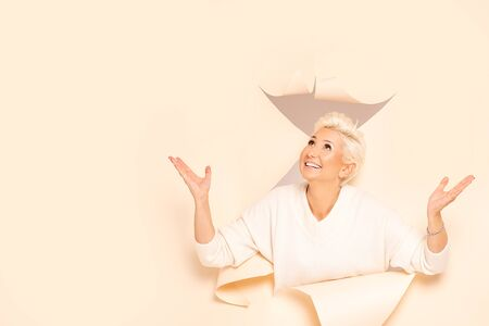 Mid aged actress showing emotions of joy. Blonde model in studio smiling , coming out of the beige background. Human expression. A lot of copy space. 版權商用圖片