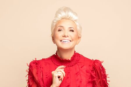 Fashion portrait of adult woman with short blond hair posing in red elegant shirt over beige background in studio. Middle age lady in glamour makeup.