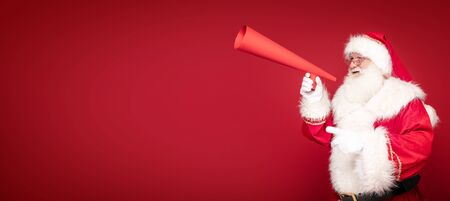 Photo of real Santa Claus screaming through a huge red megaphone.. Merry Christmas and Happy New Year concept. A lot of copy space.