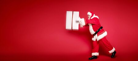 Photo of real Santa Claus with a huge red gift box. Merry Christmas and Happy New Year concept.A lot of copy space.