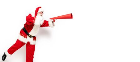 Photo of real Santa Claus running with red megaphone in hand isolated on white studio background. Christmas time.