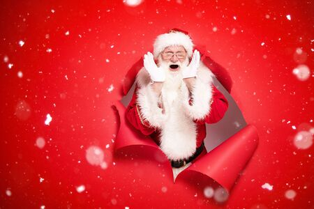 Santa Claus , the real one, comes out of the red studio background with emotional face. Christmas time.