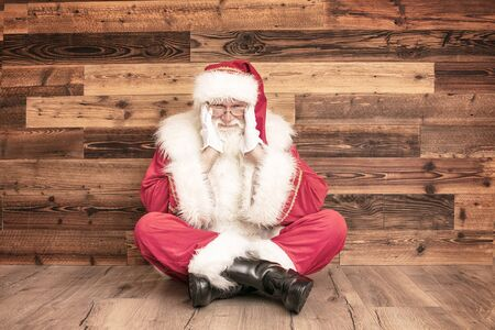 Tired real Santa Claus in red cap on wooden wall, looking at camera, sitting and resting. Merry Christmas and Happy New Year concept. Emotions and expression.