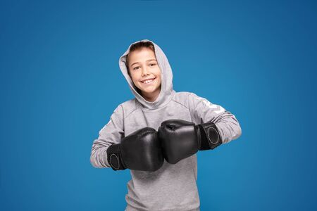 Young child sportsman in boxing gloves. Fitness, energy health. Sportswear fashion.