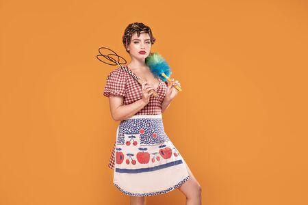 Ama de casa enojada sostenga un cepillo de plumero de colores y un batidor de alfombras. Servicio de limpieza. Mujer de servicio de limpieza Concepto de higiene. Foto de archivo